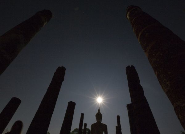 A Buddha statue in Wat Mahathat is silhouetted by a full moon during the annual Loy Krathong festival in Thailand's Sukhothai Province on November 12, 2008. The Thai tradition of Loy Krathong started off in the ancient capital of Sukhothai