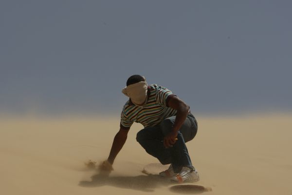 An Egyptian boy sand-boards in Al Katania dunes, about 80 km (50 miles) southwest of Cairo, March 27, 2009. REUTERS/Tarek Mostafa (EGYPT SPORT TRAVEL IMAGE OF THE DAY TOP PICTURE) BEST QUALITY AVAILABLE