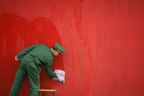 A Chinese paramilitary policeman cleans a wall in Beijing February 24, 2006. At next month's meeting of parliament, the government is likely to announce yet another double-digit increase in military spending as Beijing tries to transform its armed forces
