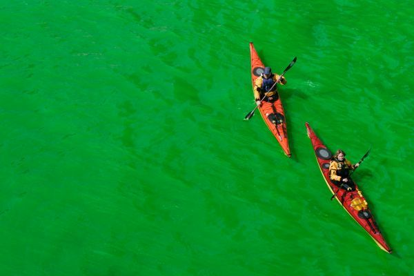 People in kayaks navigate the Chicago River after it was dyed green as part of the city's annual St. Patrick's day celebrations in Chicago March 11, 2006. REUTERS/John Gress