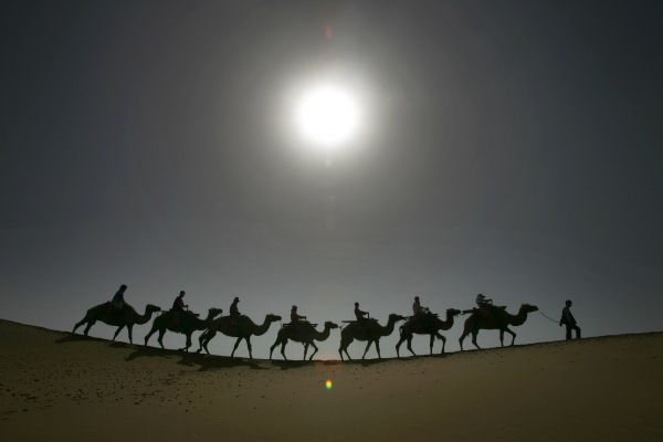 Tourists travel on camels in Tengeri Desert, on the outskirts of Zhongwei, China's Ningxia Hui Autonomous Region, June 23, 2006