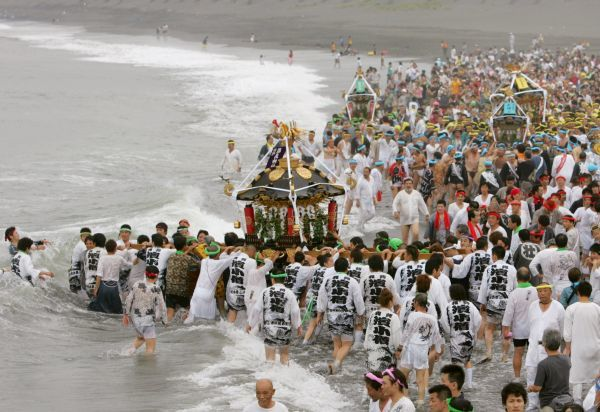 Revellers carrying portable shrines enter the ocean during the Hamaori festival in Chigasaki, south of Tokyo July 17, 2006. Revellers carried portable shrines into the water to purify them during the annual festival marking the beginning of summer