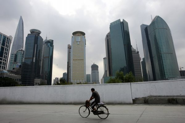 A worker rides his bicycle at Pudong, Shanghai's new financial centre, October 20, 2008