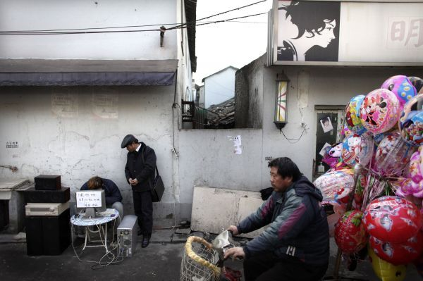 A balloon seller rides his bicycle past a man offering music download services to a customer in Shanghai January 22, 2009