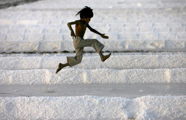 A worker's son plays in a salt pan near Bhavnagar, in the western Indian state of Gujarat March 5, 2009. REUTERS/Arko Datta (INDIA)