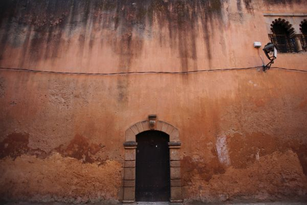 A wooden doorway in a terraccota-coloured wall of a narrow street at dawn in the Old Town of Rabat in this picture taken April 3, 2009. REUTERS/Steve Crisp (MOROCCO SOCIETY TRAVEL)