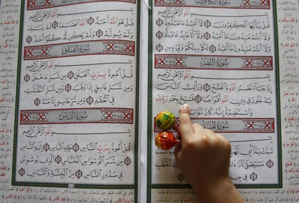 A boy holds sweets as he reads the Koran in a mosque during the Muslim fasting month of Ramadan, in Amman August 22, 2009