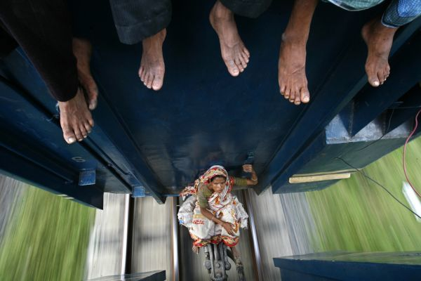 A woman sits between carriages as the train travels to Mymensing from Dhaka September 20, 2009