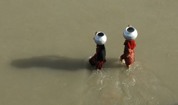 Nomad women carry metal pitchers filled with drinking water on the banks of river Balol on the outskirts of Jammu October 12, 2009. Groundwater levels in northern India have fallen about 20 percent more than expected because of excessive pumping