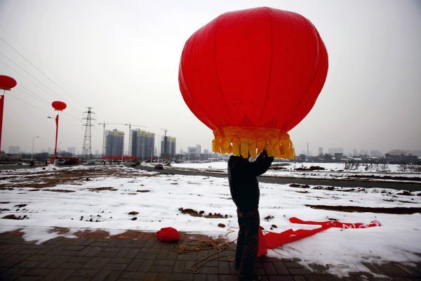 A worker installs lanterns to decorate the site of an opening ceremony for a newly-built highway in Luoyang, Henan province November 15, 2009. REUTERS/Carlf Zhang (CHINA SOCIETY)