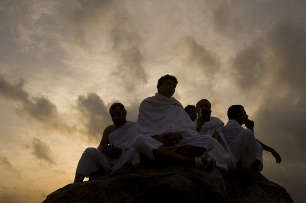 Muslim pilgrims sit on a rock on Mount Mercy on the plains of Arafat outside the holy city of Mecca November 26, 2009