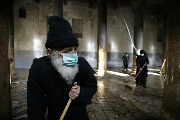 A Greek Orthodox priest (L) sweeps inside the Church of Nativity, the site revered as the birthplace of Jesus, ahead of Orthodox Christmas in the West Bank town of Bethlehem December 29, 2009