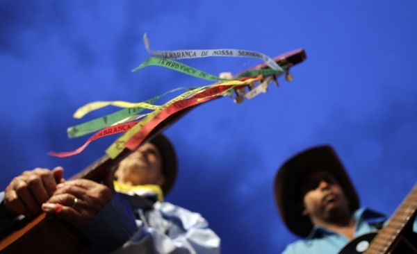 Revelers play their guitars decorated with ribbons commemorating Our Lady, the mother of Jesus Christ, during a national gathering of Folia de Reis (Revelry of Kings) bands in Brasilia January 29, 2010