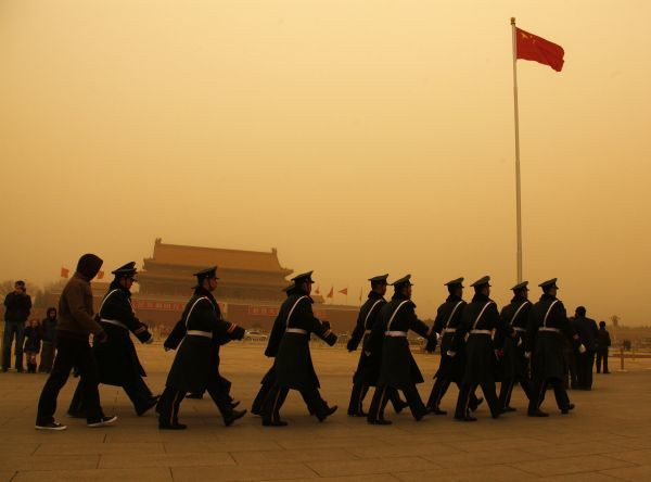 Paramilitary policemen march in formation on Tiananmen Square during a large dust storm in Beijing March 22, 2010