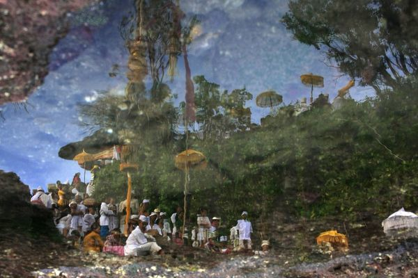 Balinese Hindu devotees gathering on the Tanah Lot temple are reflected on a puddle of sea water near Tabanan on Indonesia's resort island of Bali for the celebration of the temple anniversary May 29, 2010
