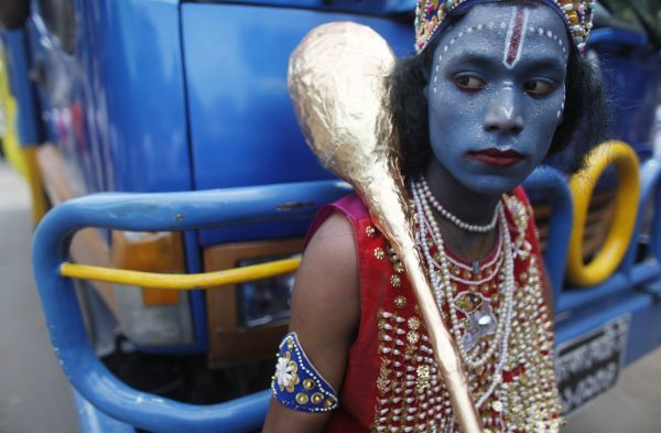 A boy dressed as Hindu Lord Krishna waits to participate in a rally in front of a temple during Janmashtami festival celebrations in Dhaka September 1, 2010