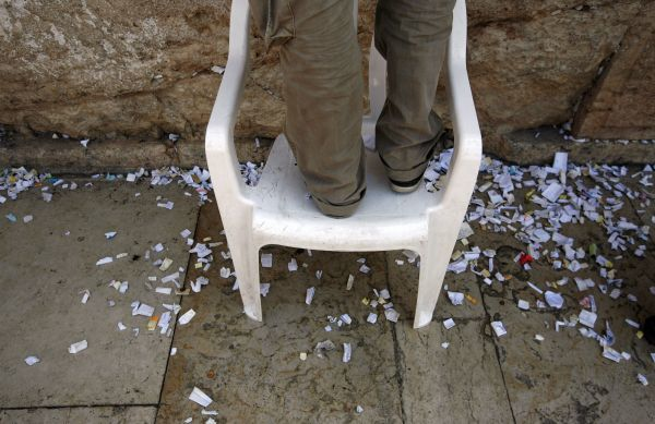 A worker stands on a chair as he removes notes from the cracks of the Western Wall, Judaism's holiest prayer site, in Jerusalem's Old City September 5, 2010