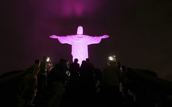 "The statue of Christ the Redeemer is lit up in pink for the start of the national campaign ""Pink October"" to raise awareness for breast cancer in Rio de Janeiro October 5, 2010"