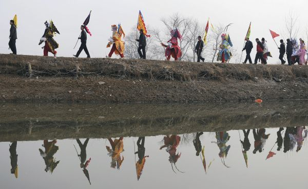 "Villagers dressed in traditional costumes march along a river during a ""Zoumadeng"" performance, on the fourth day of the Chinese Lunar New Year at Luo village of Wuhu, Anhui province February 6, 2011"