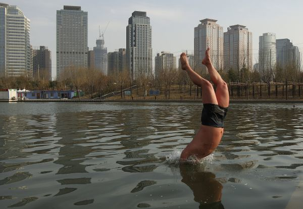 A winter swimmer jumps into a canal in Zhengzhou, Henan province March 3, 2011. REUTERS/Donald Chan (CHINA - Tags: SOCIETY)