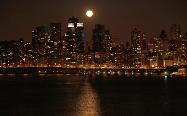 "A full moon rises over the skyline of Manhattan along the Hudson River in New York, March 19, 2011. Saturday sees the rise of a full moon called a ""Super Moon"" when it arrives at its closest point to the Earth in 2011, a distance of 221"