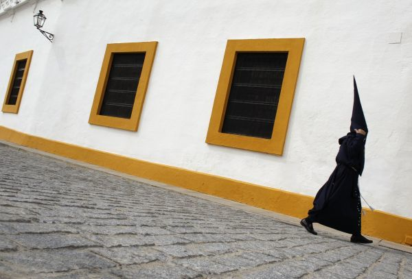 "A penitent walks to a church before taking part in the procession of ""El Baratillo"" brotherhood during Holy Week in the Andalusian capital of Seville, southern Spain, April 20, 2011"