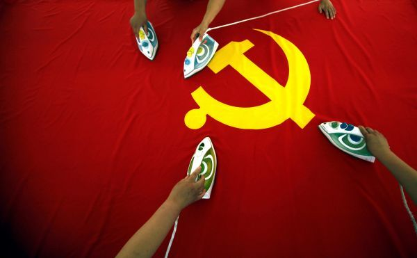 Workers use electric irons to smooth out a Communist Party of China flag on a table at the Beijing Jingong Red Flag factory located on the outskirts of Beijing June 28, 2011