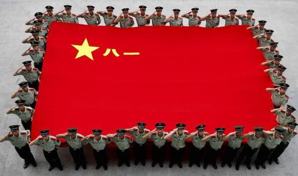 Paramilitary policemen salute as they hold a Chinese People's Liberation Army (PLA) flag to celebrate the 84th anniversary of the founding of the PLA, which falls on August 1, in Hangzhou, Zhejiang province, July 30, 2011. Picture taken July 30, 2011