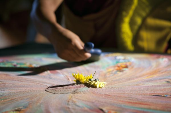 Margarita flowers are seen in the middle of a sand Mandala as a Tibetan monk sweeps the sand with a brush during the First Tibetan Cultural Maya meeting in the Riviera Maya at Playa del Carmen September 11, 2011