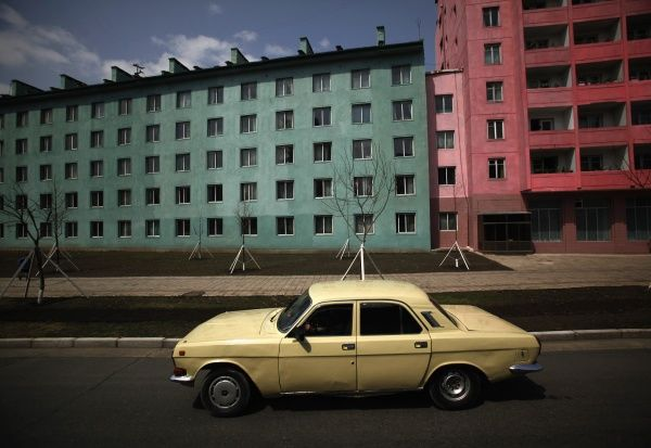 A car drives past residential buildings in Pyongyang April 11, 2012. REUTERS/Bobby Yip (NORTH KOREA - Tags: POLITICS TRANSPORT)