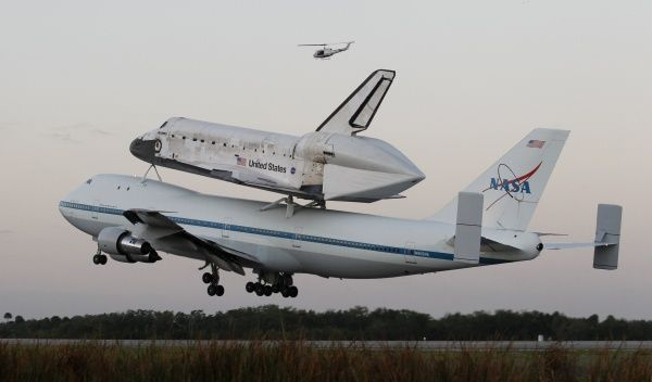 The space shuttle Discovery, attached to a modified NASA 747 aircraft, takes off headed for its final home at The Smithsonian National Air and Space Museum's Steven F