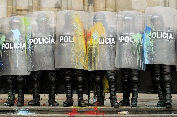 Riot policemen stand guard after getting splattered by paintballs from student protesters during clashes on International Workers' Day, or May Day, at the central square of Bogota May 1, 2012