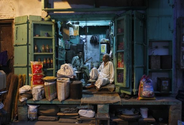 A shopkeeper (R) and his sales assistant wait for customers inside a family-owned grocery store in an alley in the old quarters of Delhi September 17, 2012