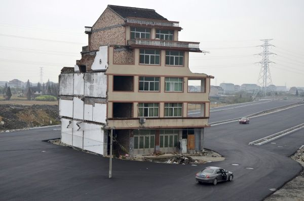 A car stops beside a house in the middle of a newly built road in Wenling, Zhejiang province, November 22, 2012