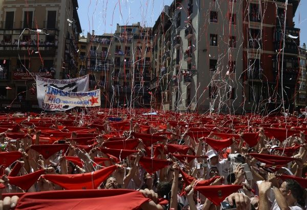 Revellers hold up their red scarves during the start of the San Fermin festival in Pamplona July 6, 2013