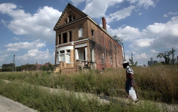 A man walks past a vacant, boarded-up home surrounded by overgrown grass in a once vibrant neighborhood, near downtown Detroit, Michigan July 19, 2013