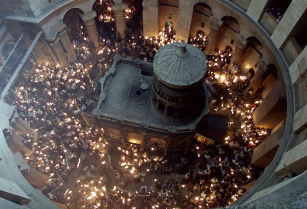 "A trail of fire spreads as thousands of Orthodox Christians light candles inside the Church of the Holy Sepulchre surrounding the Tomb of Jesus (C) as the ""Ceremony of the Holy Fire"" is celebrated April 14, 2001"