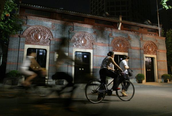 Chinese cyclists pedal past the site of the first National Congress of the