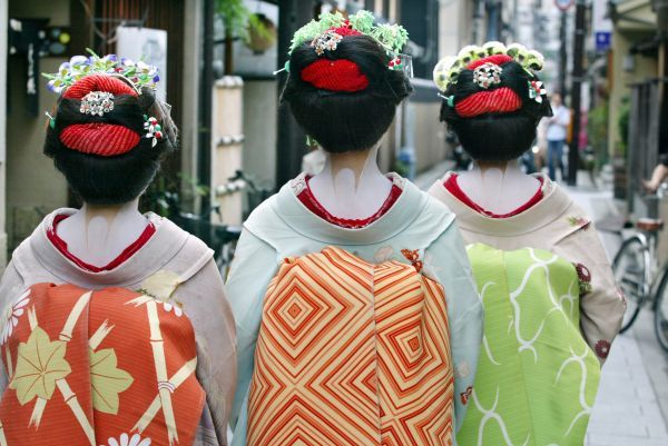"Japanese tourists Naomi Sato (R), Hitomi Abe (C) and Kumi Tamizane, in rented ""Maiko"" costumes, walk down a street in the Japanese ancient capital of Kyoto July 5, 2003"