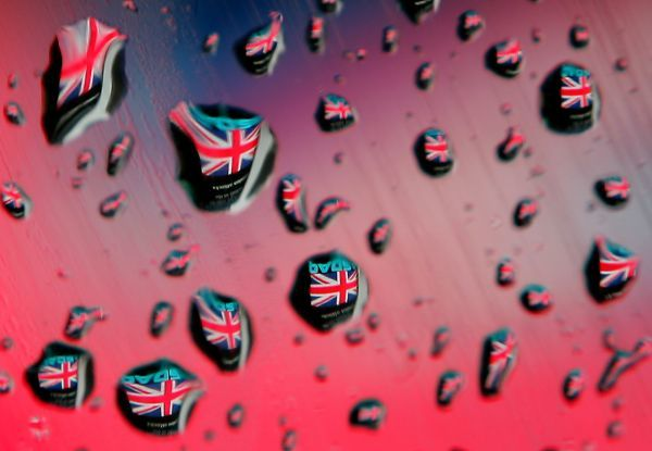 The Union Jack is reflected in raindrops on a car window from the electronic message sign at the NASDAQ Market Site in New York's Times Square July 8, 2005, which has been displaying the flag as part of a tribute to victims of Thursday's