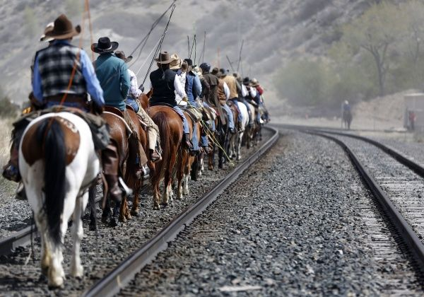 Wranglers travel up a train rail line during Montana Horses' annual horse drive outside Three Forks, Montana, May 6, 2012. The Mantle family, who own Montana Horses, held their last horse drive where they rounded up approximately 300 horses