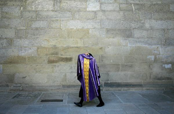 A nun walks with a priest's suit in her hand inside the Santiago de Compostela's Gothic cathedral in northern Spain July 21, 2006