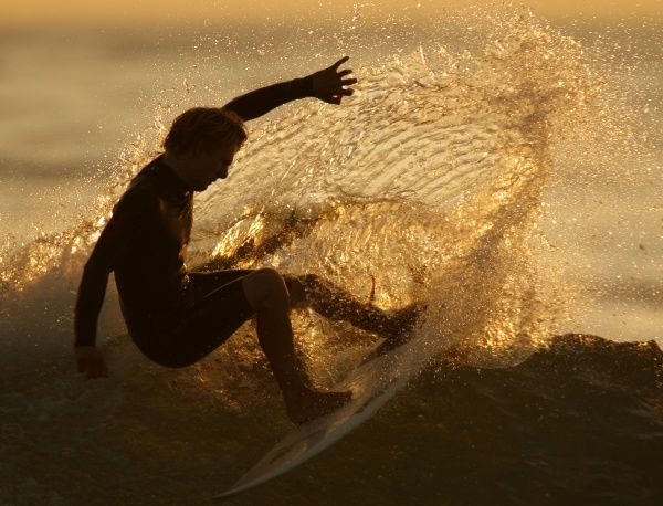 A surfer is silhouetted as he cuts a turn on a wave during a summers evening on the Pacific Ocean in Solana Beach, California August 8, 2006. REUTERS/Mike Blake(UNITED STATES)