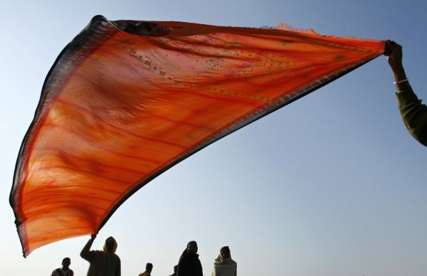 Hindu devotees hold up clothes to be dried during the Ardh Kumbh Mela, or Half Pitcher Festival in Allahabad city January 5, 2007
