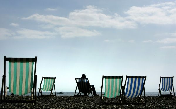 A man sits on a deck chair in warm Easter weather on Brighton beach in southern England April 7, 2007. REUTERS/Luke MacGregor (BRITAIN)