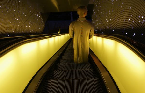 A monk stands on the escalator of a shopping mall at the Peak in Hong Kong May 29, 2007, about a month before the 10th anniversary of Hong Kong's handover to Chinese rule. REUTERS/Paul Yeung (CHINA)