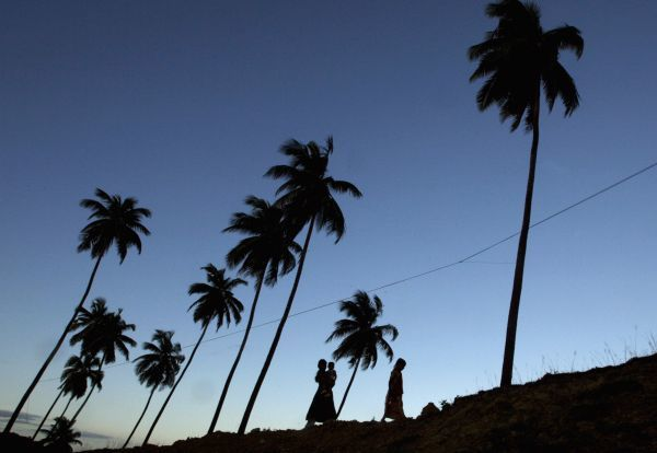 Girls walk along the sea shore in Port Blair, capital of India's Andaman and Nicobar islands, September 8, 2007. REUTERS/Adnan Abidi (INDIA)