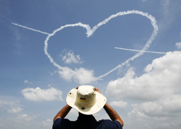 A man takes a photo as members of the Republic of Singapore Air Force (RSAF) Black Knights aerobatic team form a heart shape using smoke trails during a performance at the Singapore Air Show in Singapore February 19, 2008. REUTERS/Vivek Prakash