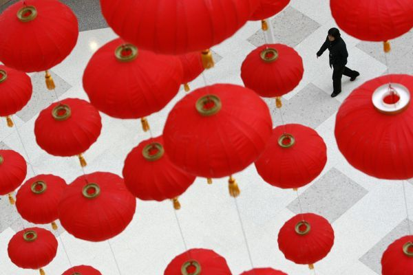 A woman walks under red lanterns at a shopping mall in Shanghai January 16, 2009