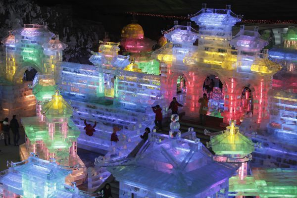 Visitors walk on ice sculptures in the shape of traditional Chinese buildings at the Ice Lantern Art Festival held on the outskirts of Beijing January 18, 2009. Chinese people all over the world prepare to usher into the Lunar New Year on January 26